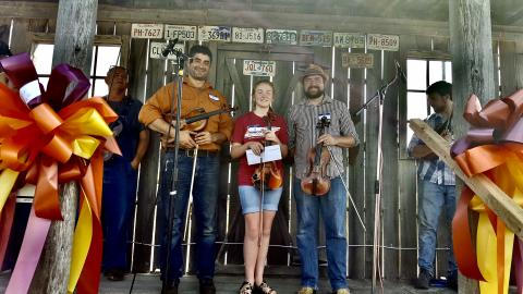 picture of an old front porch with 2019 Fiddle Contest Winners: Eric Nafzigar (2nd), Kasey Moore (1st), Austin Stovall (3rd)