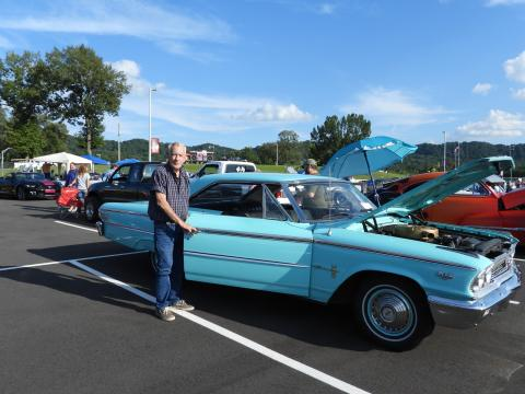 Man standing next to a vintage car
