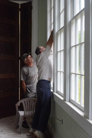 Preservation Union County volunteers Stan Bullen and Joe Rogers work on the windows at Oak Grove School in Sharps Chapel.