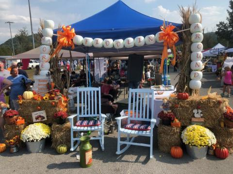 picture of Rocky Top Award winner for best portrayal of the festival theme, More Fiddlin' Around, was A& B Bookkeeping and Tax Service. Picture has two white rocking chairs in front of a banner made of pumpkins that say More Fiddlin' Around.  The rocking chairs are surrounded by mums in washtubs with a fiddle displayed on haybales.