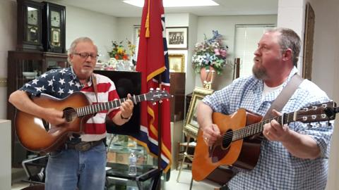 Two men singingcountry music in a museum