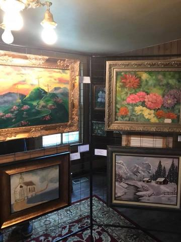 four paintings, one of flowers, one winter forest scene, one chuch scene, one of mountains with a religious cross