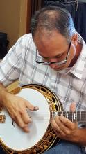 Stuart Wyrick is tuning and picking a banjo