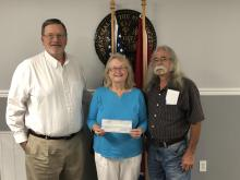Picture of two males with a female in between.  The female is holding a check.  The males are the mayor and vice mayor of Plainview City.  Plainview made a donation to Imagination Library