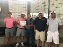 Men receiving award for golf tournament first place.