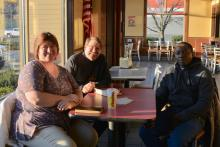 The Rev. Kathy Chesney, Fr. Steve Pawelk and Josiah Kimani gather for prayer and Bible study at Hardee's in Maynardville.
