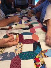 Sharps Chapel Quilters work on a quilt started by a woman who passed away due to cancer.