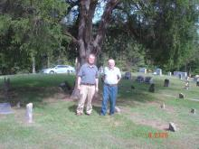 Jay Ricketts and John Cabage standing near the burial site of Alfred Gallatin Rickets in Cabbage Cemetery