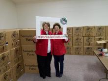 Operation Christmas Child Area Coordinator Amie Winstead and drop-off team leader Holly Simmons pose for a picture with filled boxes ready to ship.