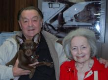 Earl and Judy Stowers with Lucky the pup stand in front of a photo of their Weimarener, Sasha. Earl says Sasha is driving his van and making a left-hand turn.