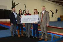 Breann Welch (second from left) of Sweet Southern Tumbling receives a small business loan check from Clinch Powell.