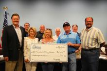 Phil Ruth presents a check for the Luttrell Music Festival to organizer Mayme Taylor