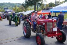 An antique tractor in a parade at a festival