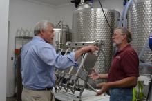 State USDA Director Jim Tracy gets a behind-the-scenes look at the Winery at Seven Springs Farm from Rick Riddle.